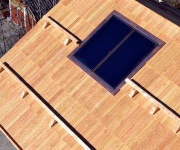 Couverture en bardeaux et arrêts de neige en mélèze, avec intégration des panneaux solaires